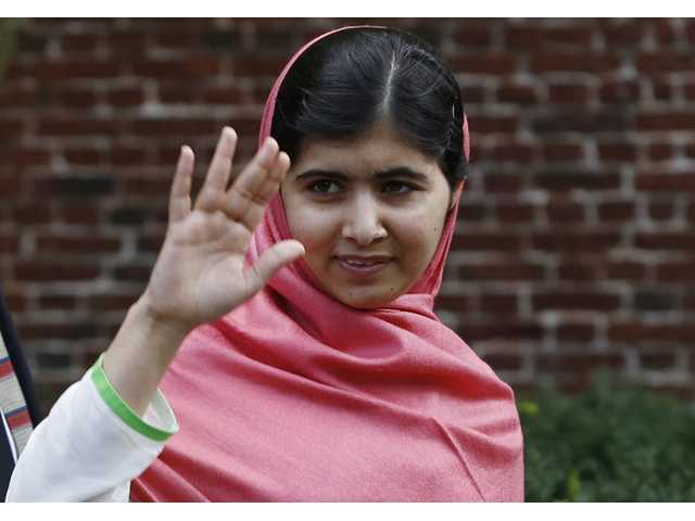Malala Yousafzai, waves to onlookers after speaking at a news conference at Harvard University campus in Cambridge, Mass. on Friday.