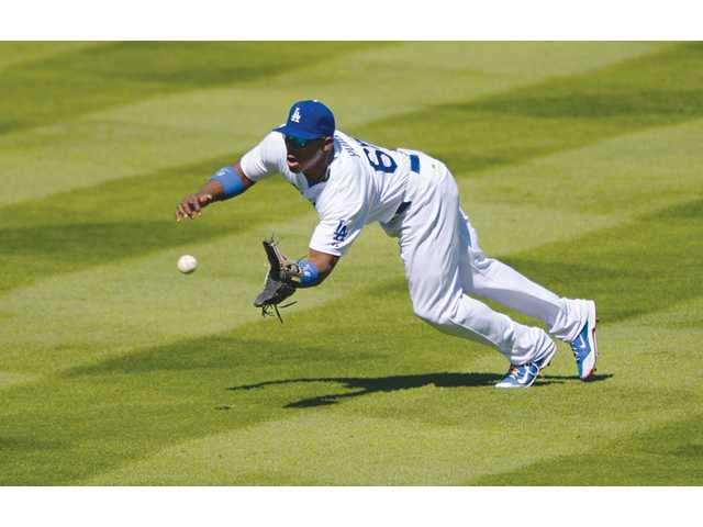 Los Angeles Dodgers right fielder Yasiel Puig makes a diving catch against the Colorado Rockies on Sunday in Los Angeles.