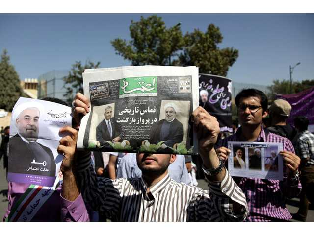 "A supporter of Iranian President Hassan Rouhani, holds a local newspaper with a headline that reads, ""historic call from a return flight,"" upon his arrival from the U.S. near the Mehrabad airport in Tehran, Iran on Saturday."