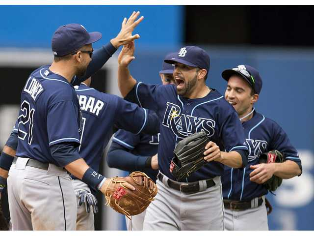 Tampa Bay Rays James Loney, left, Matt Joyce, center, and Sam Fuld, right, celebrate after the Rays defeated the Toronto Blue Jays in Toronto on Sunday.
