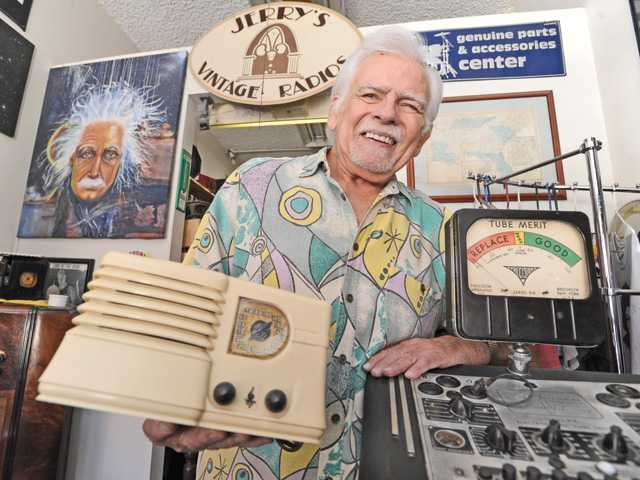 Jerry Simpson holds a 1941 Emerson Plaskon Ingraham radio as he stands next to a vintage tube tester in the front lobby of his store in Santa Clarita.