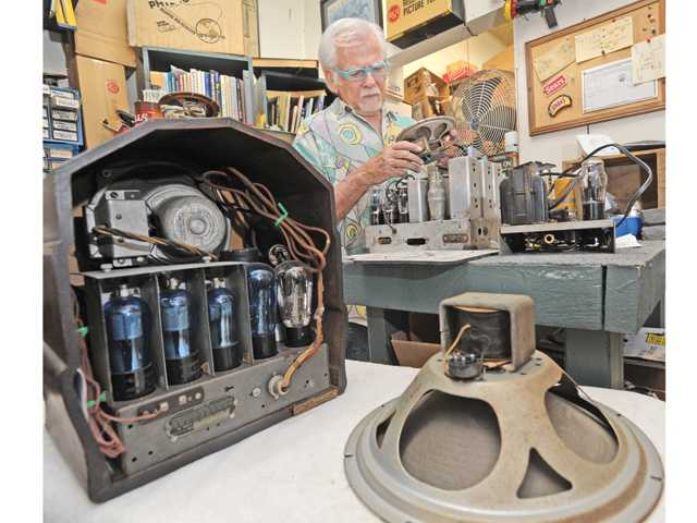 Jerry Simpson examines vintage tube radios and equipment in the work room of his shop, Jerry's Vintage Radio.