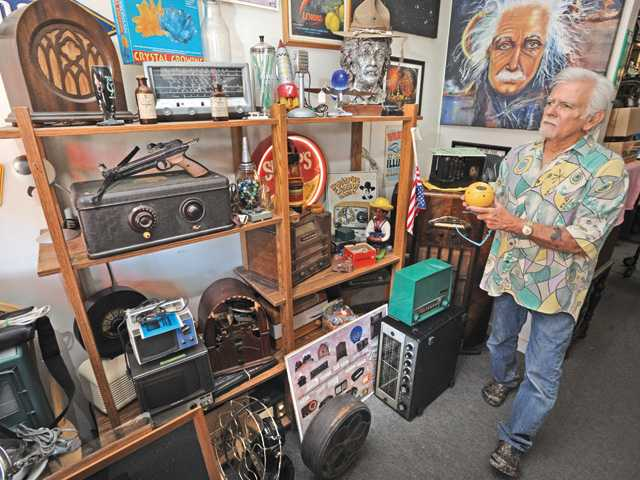 Jerry Simpson with a variety radios and collectables in the front lobby of his store in Santa Clarita.