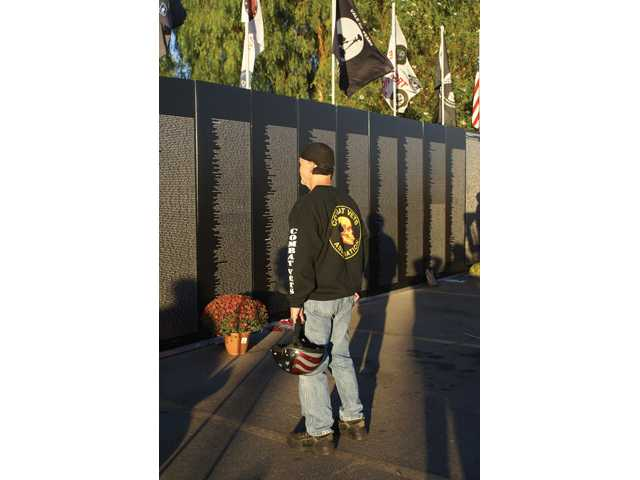 A Vietnam veteran looks at the Traveling Vietnam Memorial Wall on Sunday at the Westfield Valencia mall.