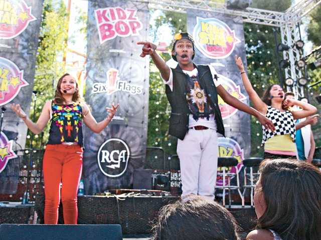 KIDZ Bop Kids, Eva Agathis, Elijah Johnson, and Kiana Brown (left to right) take center stage while performing during the KIDZ Star USA Talent Search finale event in Six Flags Magic Mountain Saturday. Signal photo by Natalee Ayala
