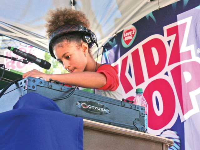 DJ Young 1 spins and mixes with her turn table during the KIDZ Star USA Talent Search finale event in Six Flags Magic Mountain Saturday. Signal photo by Natalee Ayala