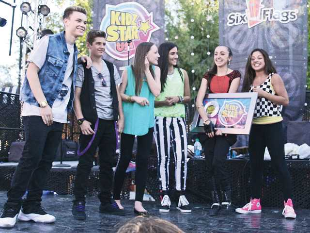 Dallas Wayde, Liam Gregory, Eileen Stewart, Tina Siciliano, Isabel Lacatus and Kiana Brown appear on stage after the KIDZ Star USA Talent Search winner was announced during the finale event in Six Flags Magic Mountain Saturday. Lacatus holds her grand prize. Signal photo by Natalee Ayala