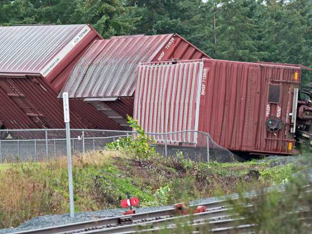 A man examines four rails cars on the Boeing campus that were tipped over by a funnel cloud which hit several locations near Tacoma Monday.