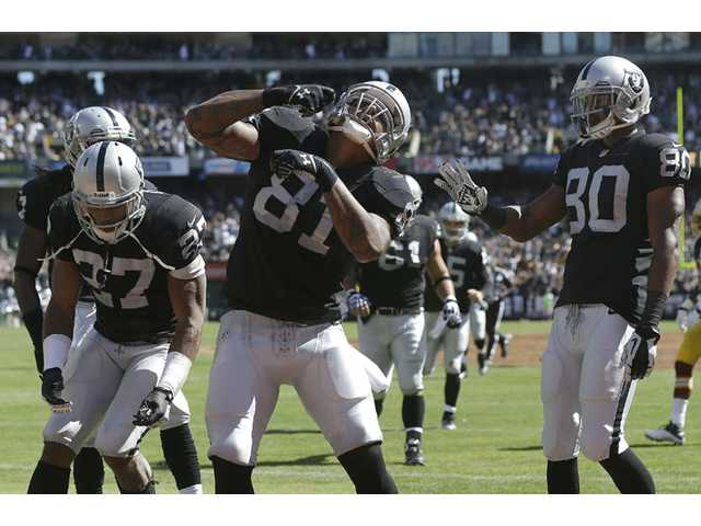 Oakland Raiders tight end and former College of the Canyons player Mychal Rivera (81) celebrates with teammates after scoring on an 18-yard touchdown pass on Sunday in Oakland.