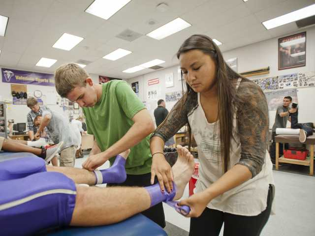 Andrew Thompson and Jesse Pascolla wrap a football player's ankles before a practice at Valencia High School Sports medicine classroom on Tuesday. Photo by Charlie Kaijo.