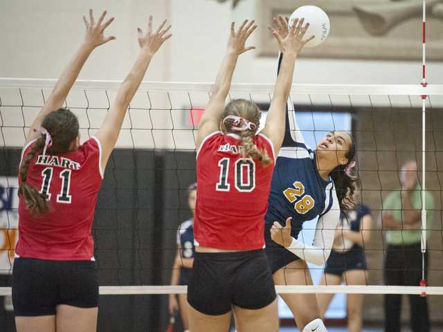 West Ranch outside hitter Alexis Clewis (28) spikes the ball past Hart defenders Brooke Boron (11) and Chase Tengberg (10) on Tuesday night at West Ranch High School.  West Ranch won 3-1.