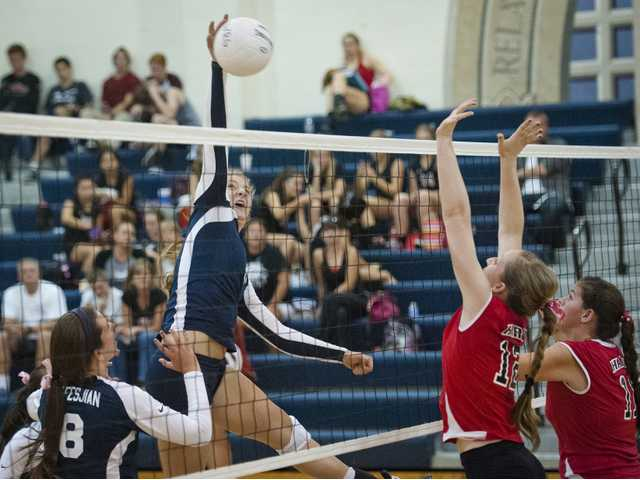Middle Alexa Hesseldenz, center, spikes the ball against Hart's Corrine Holloway (12) and Brooke Boron (11) on Tuesday at West Ranch.