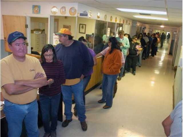 Employees of the Crow Tribe line up to receive their paychecks at the tribal offices in Crow Agency, Mont., Wednesday, Oct. 2, 2013.