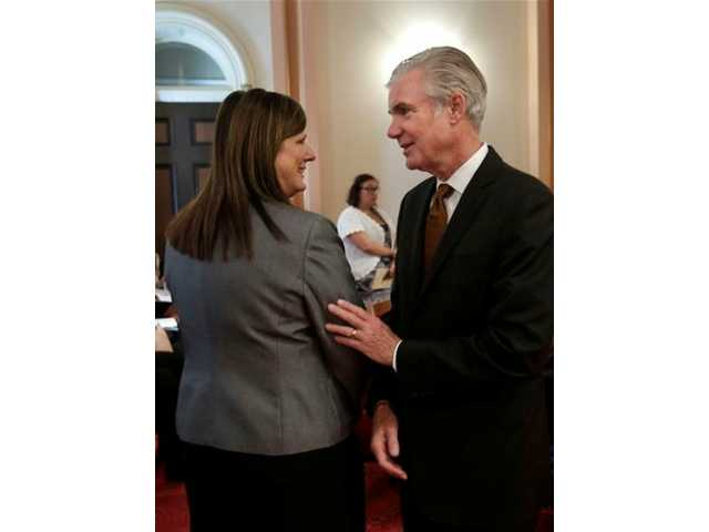 Assemblywoman Susan Bonilla, D-Concord, left, is congratulated by state schools chief Tom Torlakson, after the state Senate approved Bonilla's bill that would end traditional standardized student testing, in Sacramento, Calif., Tuesday, Sept. 10, 2013.