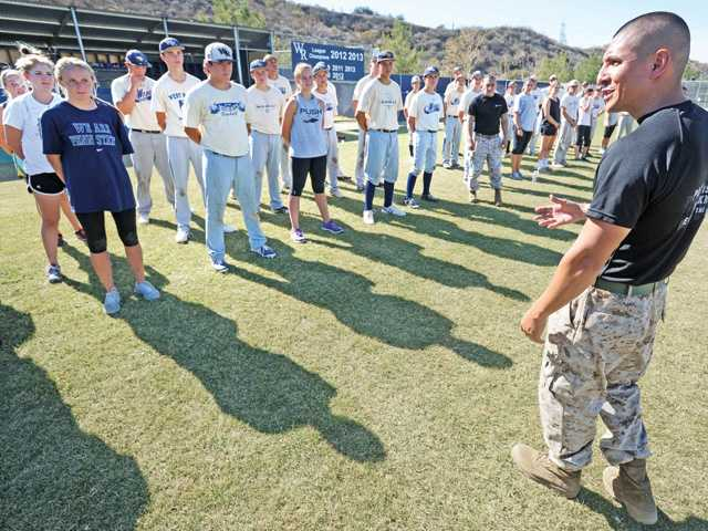 U.S. Marine Staff Sgt. Edwin Salvatierra, right, congratulates West Ranch High School baseball and softball players for their participation in a U.S. Marine boot camp held at their school Tuesday. Signal photo by Dan Watson