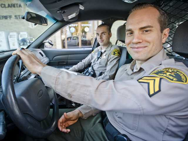 Sheriff's deputies Sean Caples (in driver's seat) and Patrick Ince at the Santa Clarita Valley Sheriff's Station on Wednesday. The two deputies ran into a burning Canyon Country condo and saved a woman inside on Monday. Photo by Charlie Kaijo.