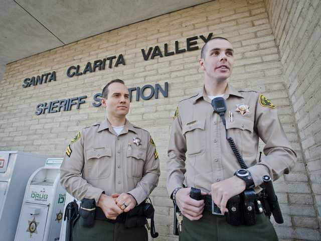 Sheriff's deputies Sean Caples (left) and Patrick Ince stand outside the Santa Clarita Valley Sheriff's Station on Wednesday. Photo by Charlie Kaijo.