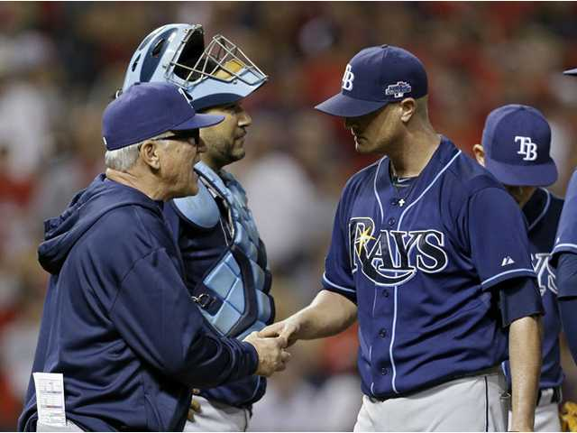 Tampa Bay Rays manager Joe Maddon, left, takes the ball from starting pitcher Alex Cobb in the seventh inning of the AL wild-card game against the Cleveland Indians on Wednesday in Cleveland.