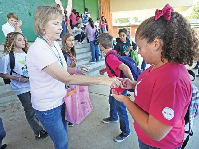 Kerry Skoczylas, left, director of SiViCS Club (Sierra Vista Caring Spirit Club) sells a pink wristband to eighth-grader Aleah Fontenette in front of dozens of Sierra Vista students who participated in the Lee National Denim Day. Photo by Dan Watson.