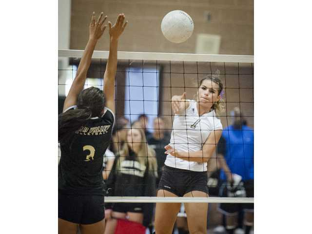 Valencia's Makena Lautner spikes the ball as Golden Valley's Juliet Gunn defends on Thursday at Golden Valley High.