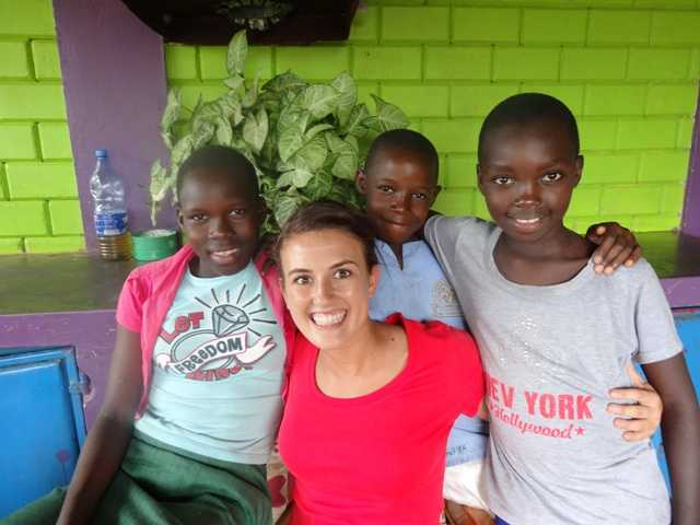 Jacey Massetto posing with three girls from an orphanage in Uganda. Courtesy photo