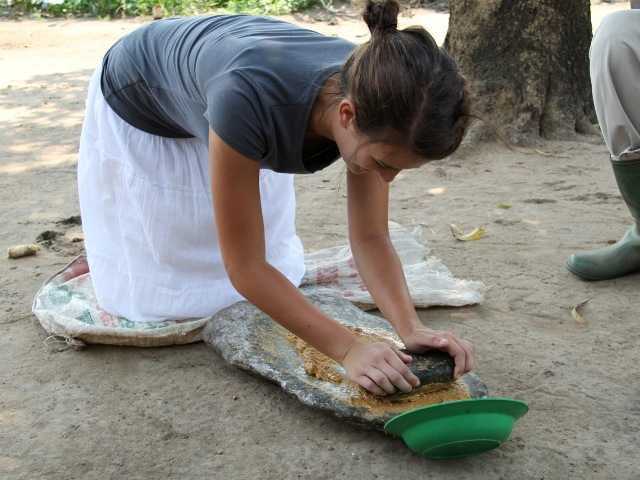 Jacey Massetto grinding corn while on a trip in Uganda. Courtesy photo