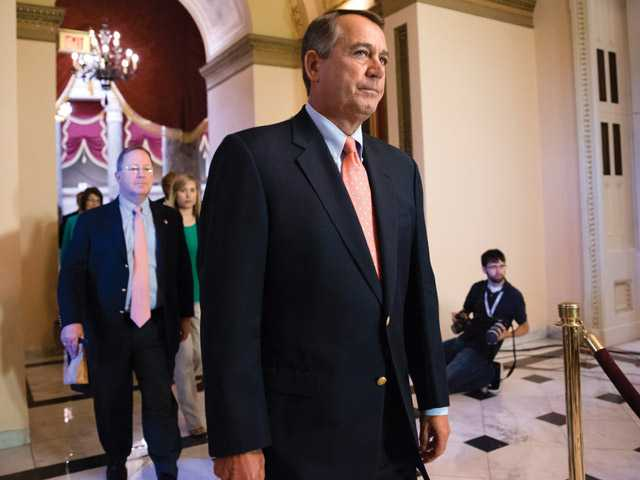 Speaker of the House John Boehner, R-Ohio, walks to the chamber as lawmakers vote to pay federal workers who have been furloughed during the government shutdown, at the Capitol in Washington on Saturday.