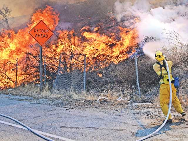 Firefighters work to control a 15-acre brush fire along the northbound Interstate 5 freeway on Saturday at The Old Road. The fire was contained near 3 p.m.