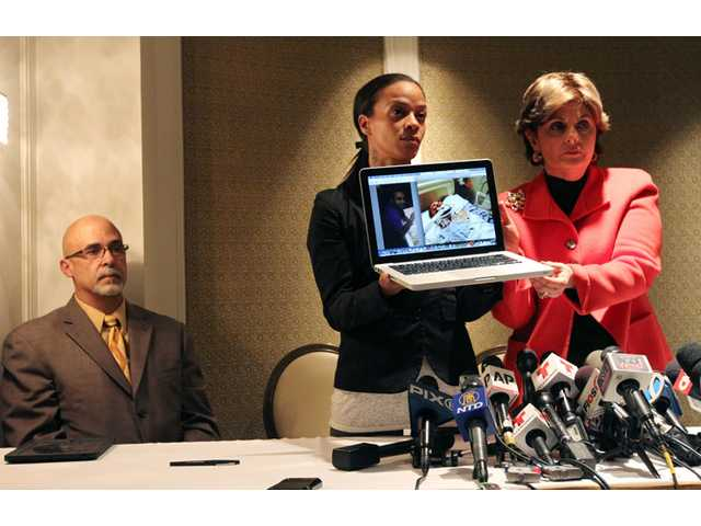 Dayana Mejia, center, and attorney Gloria Allred, right, hold up a laptop with images of Mejia's partner, Edwin Mieses Jr., during a news conference in New York on Friday.