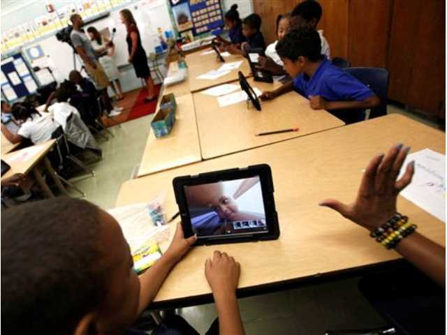 In this Aug. 27, 2013, file photo, students photograph themselves with an iPad during a class at Broadacres Elementary School in Carson, Calif.