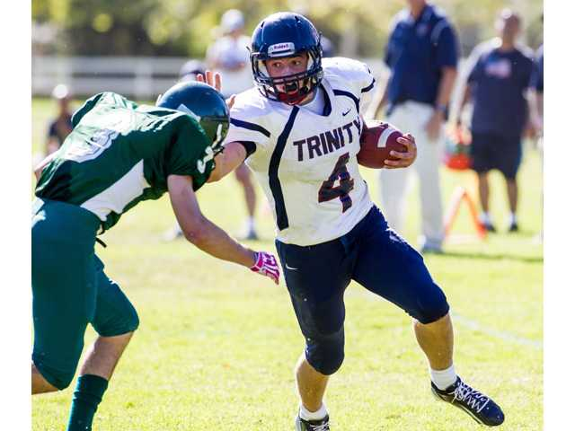 Trinity's Spencer Klehn (4) stiff arms a Ojai Valley would-be tackler on Saturday afternoon at Ojai Valley High School. The Knights won 50-6.