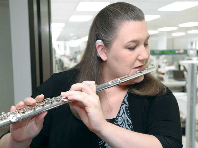 Musician and cochlear implant recipient Lisa Jordan plays her flute for the technicians manufacturing implants at Advanced Bionics hearquarters in Valencia. Signal photo by Dan Watson