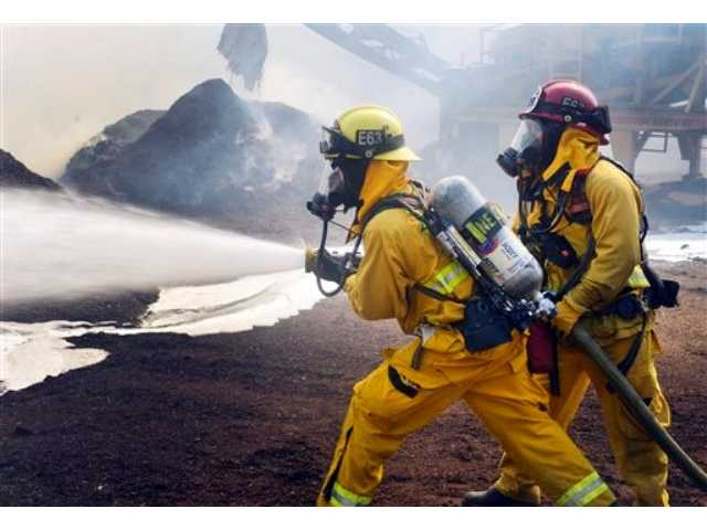 Newport Beach firefighters put out a burning mulch pile at a nursery near Santiago Canyon in Orange County, Calif. Sunday, Oct. 6.