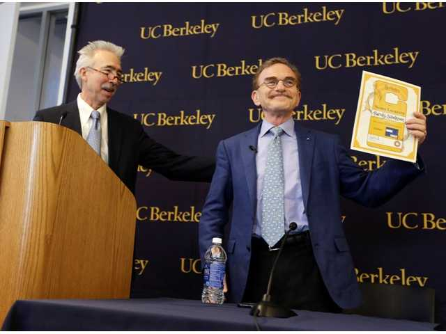 Randy Schekman, right, professor at the University of California, Berkeley, holds up his lifetime campus parking pass that he was given by Chancellor Nicholas Dirks, left, after winning the Nobel Prize in medicine during a news conference Monday, Oct. 7, 2013, in Berkeley, Calif.