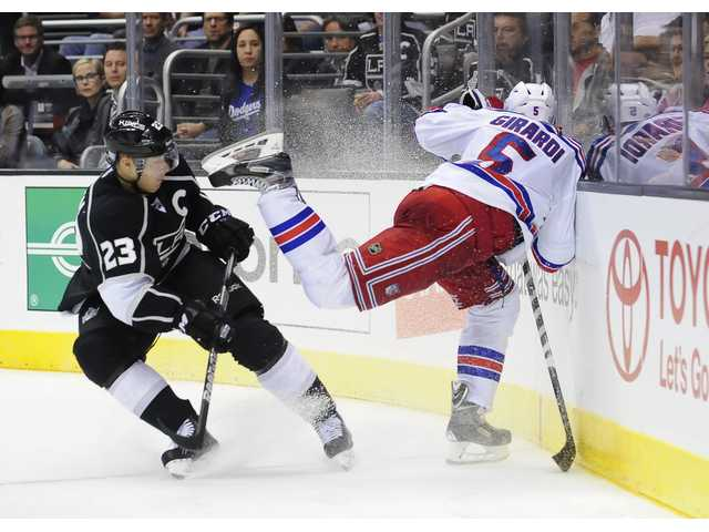 New York Rangers defenseman Dan Girardi (5) slams into the wall as he and Los Angeles Kings right wing Dustin Brown (23) pursue the puck during the second period of an NHL hockey game, Monday.