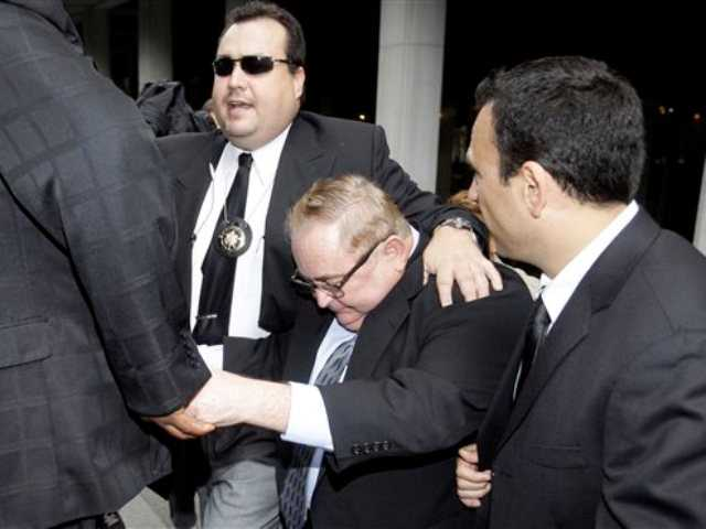 In this Oct. 21, 2010 file photo, Former Bell, Calif., city manager Robert Rizzo, is escorted from court by bodyguards after an arraignment on corruption charges. Los Angeles County district attorney says the former city manager of suburban Bell, Calif., has pleaded no contest to all 69 counts in a massive public corruption case.