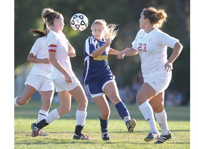 COC's Leilani Konrad (11) passes toward the goal through Bakersfield College defender at COC on Tuesday.
