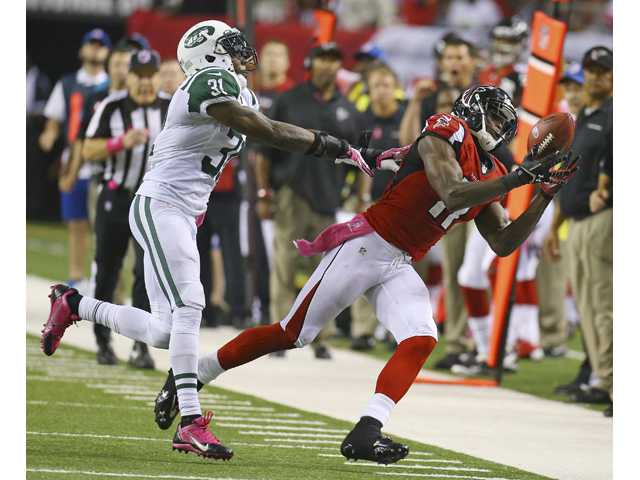 Atlanta Falcons wide receiver Julio Jones can't hold on to a pass as he is hit by New York Jets cornerback Antonio Cromartie.