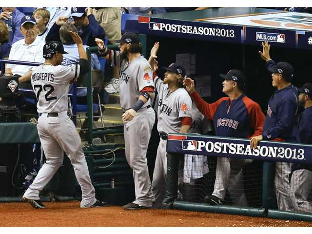 Boston Red Sox player Xander Bogaerts (72) trades high-fives with teammates in the dugout against the Tampa Bay Rays on Tuesday in St. Petersburg, Fla.