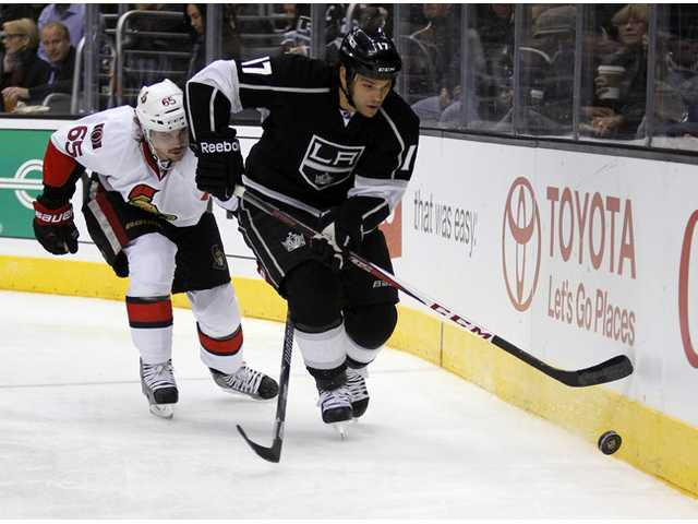 Los Angeles Kings left wing Daniel Carcillo (17) follows the puck with Ottawa Senators defenseman Erik Karlsson (65), of Sweden, defending during the second period of their NHL hockey game, Wednesday in Los Angeles.