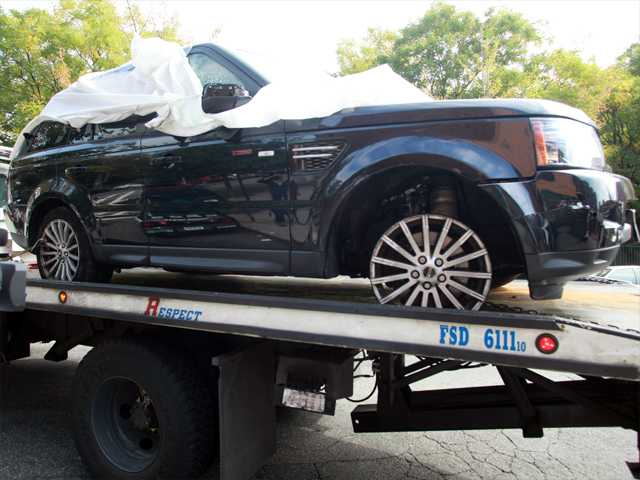 In this Oct. 5  file photo,The Range Rover involved in the bikers attack is moved from the police precinct for further police investigation in New York. An off-duty New York Police Department undercover detective apparently seen on video pounding on an SUV during a melee with motorcyclists has been arrested Tuesday.