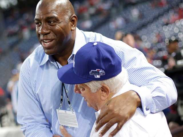 "Former NBA basketball player Earvin ""Magic"" Johnson Jr. embraces former L.A. Dodgers manager Tommy Lasorda before the Atlanta Braves and the Dodgers game, Oct. 3."