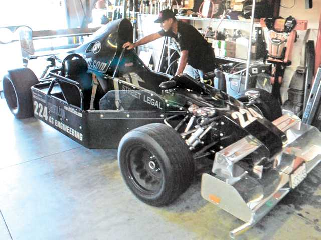 George Salazar Jr. looks at his race car at his machine shop in Valencia. Photo by Dan Watson.
