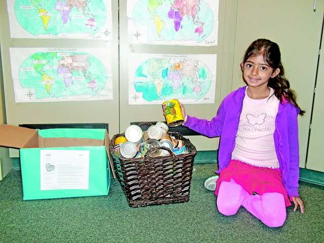 Third grader Reya Mehta helps with the canned food drive at Oaks Hills Elementary School.