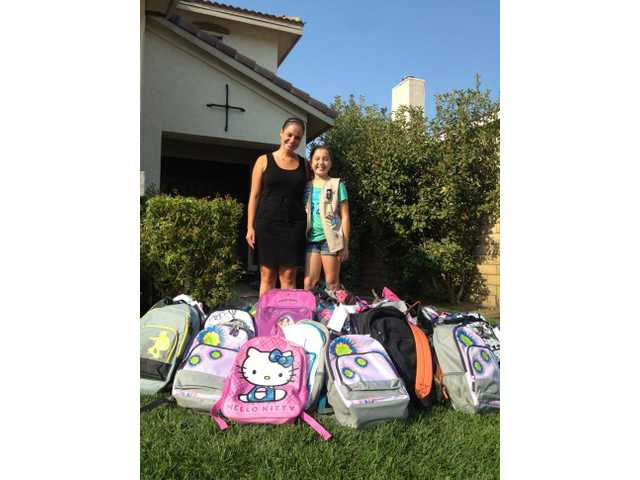 Shannon Mayock, director of marketing and communications for After-School All-Stars L.A., stands with Emilie Alber and several of the backpacks Alber donated.