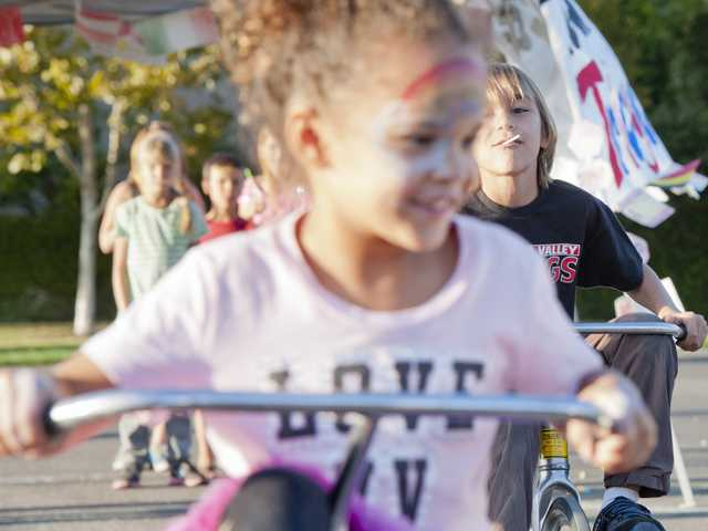 Kayla Hintz, a kindergarten student, races third grader Lucas Gomez in a Tour de France themed tricycle race for the Valencia Valley Elementary School Harvest Festival on Friday.