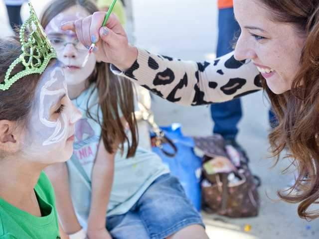 Parent volunteer Angela Diaz paints third grader Elizabeth Matchie's face at a masquerade-themed face painting booth at the Valencia Valley Elementary School Harvest Festival on Friday.