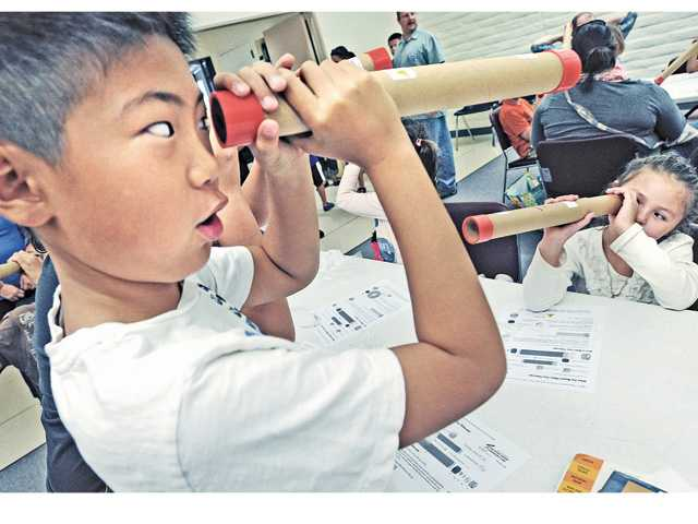 Chris Kim, 9, left, and Jenny Gallardo, 7, right, look through the refractor telescopes they constructed during the Astronomy Day activities presented by The Local Group Astronomy Club at the Valencia Library on Saturday.