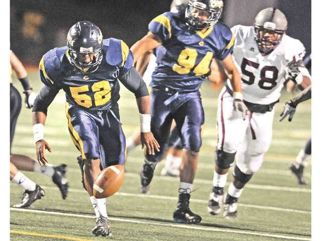 College of the Canyons linebacker Kenneth Jacobs (52) recovers an Antelope Valley College fumble to set up a score for COC in the fourth quarter at COC on Saturday.  Teammate Matt Freeman (94) looks on.