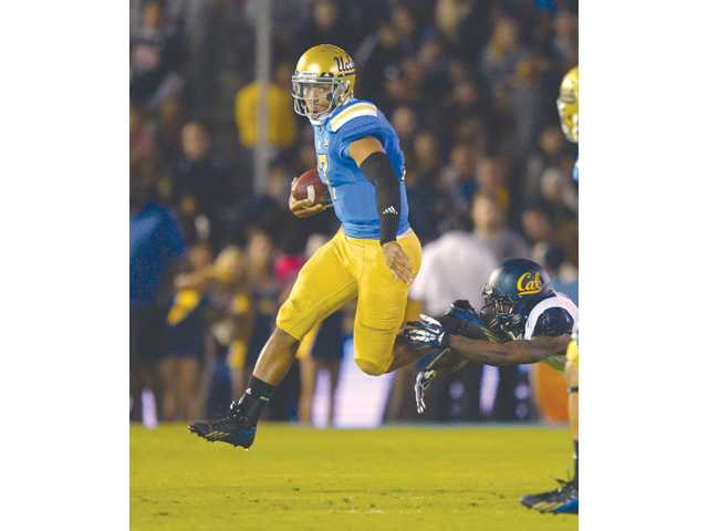 UCLA quarterback Brett Hundley escapes the tackle of California defensive back Kameron Jackson.